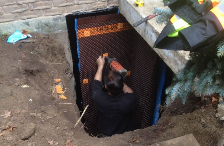 Man in hole fixing house foundation
